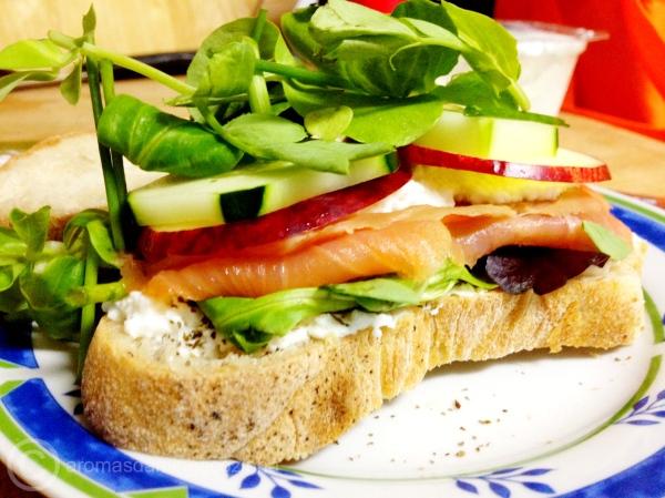Pão no prato com requeijão, salmão fumado, maçã e pepino